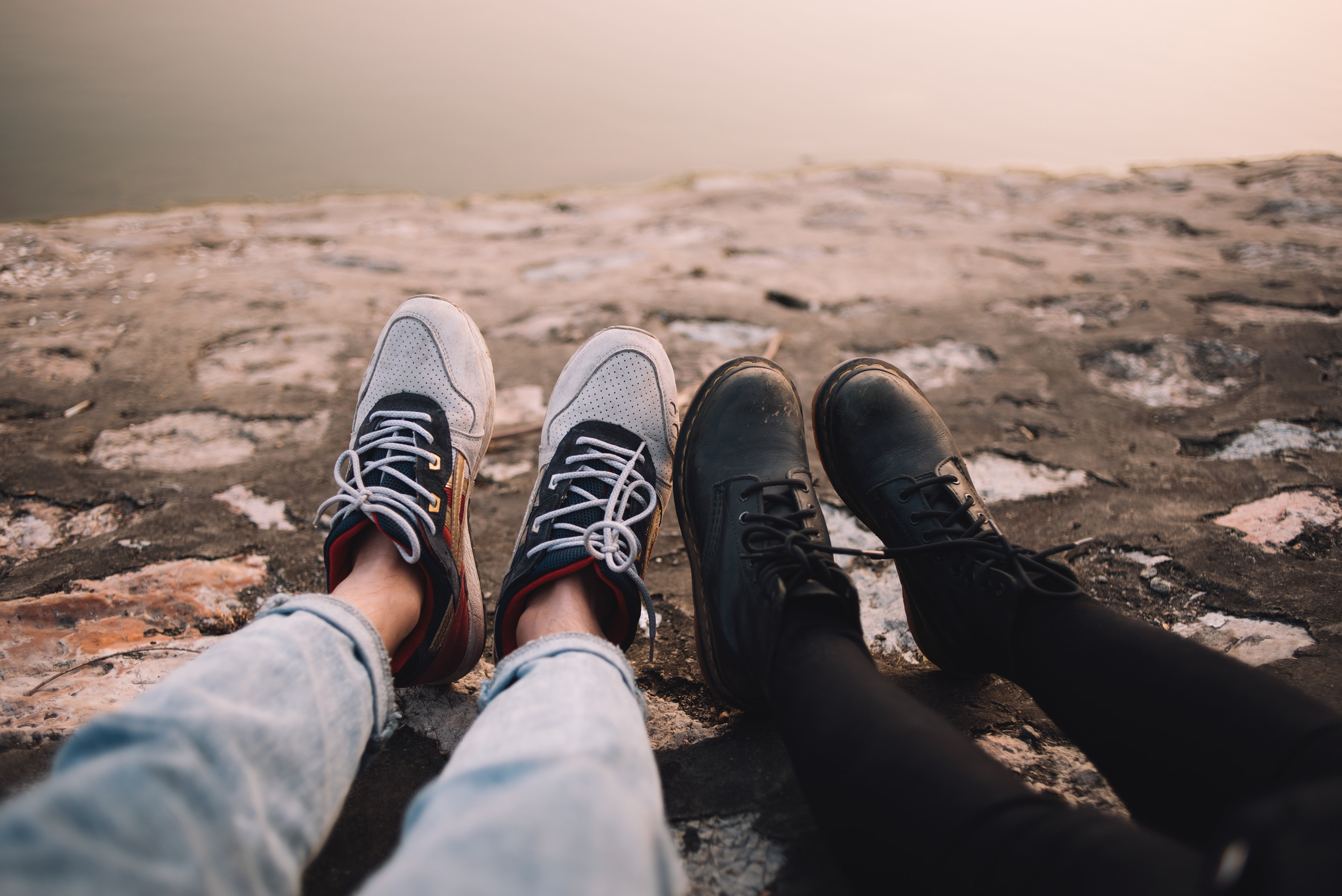 Two persons wearing pants and shoes sit on the ground at daytime