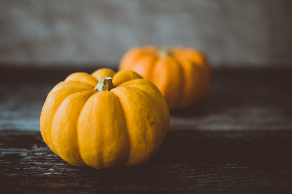 Two yellow pumpkins on a wooden table
