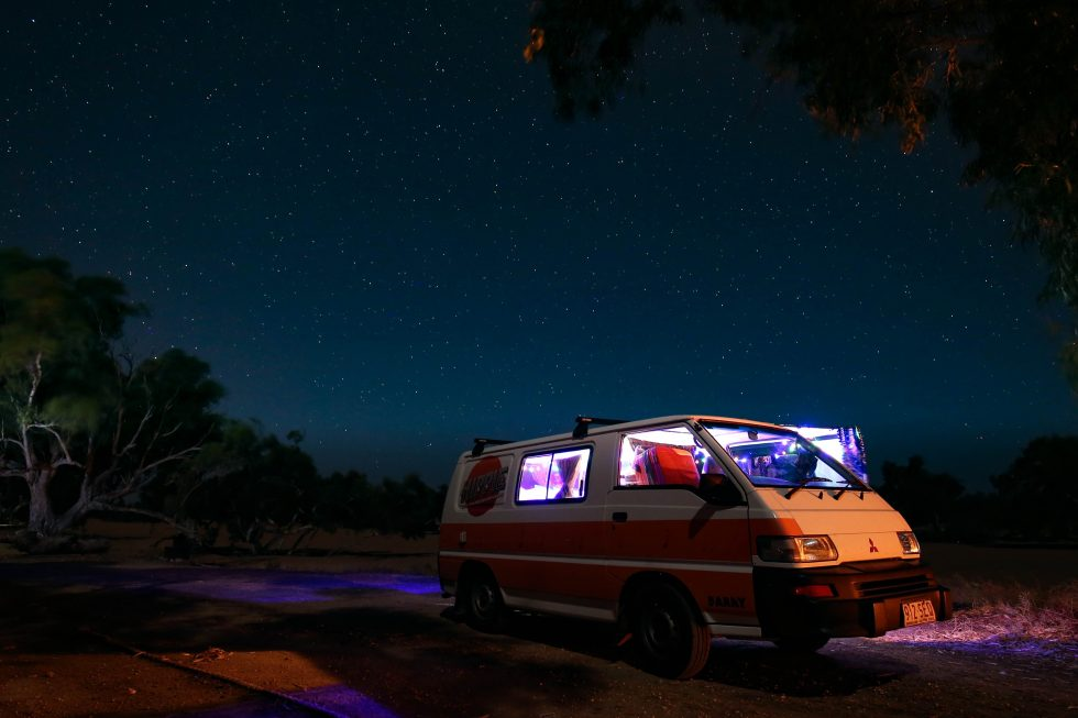 White and orange Mitsubishi Van during a starry night