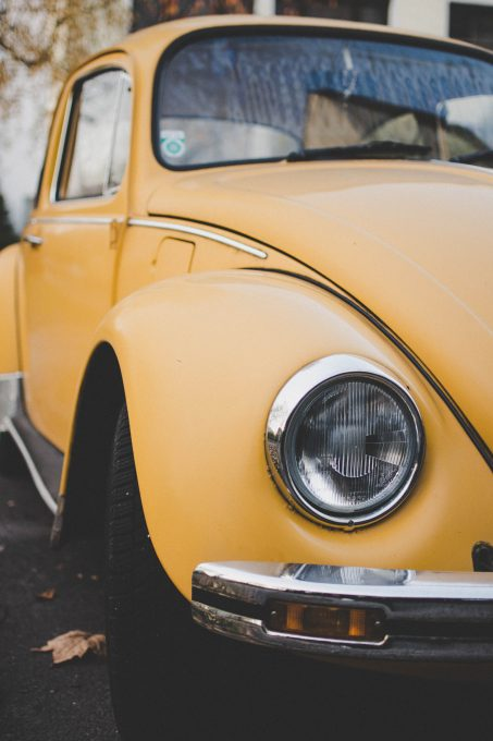 Yellow Volkswagen Beetle Coupe parked on asphalt road on an autumn day