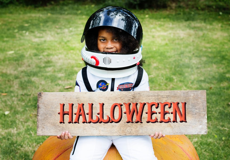 A girl in a spacesuit holding Halloween decor