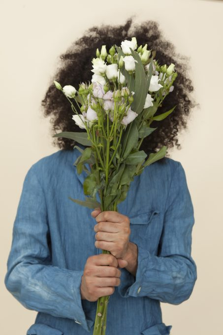 A person holding white a flower bouquet covering the face
