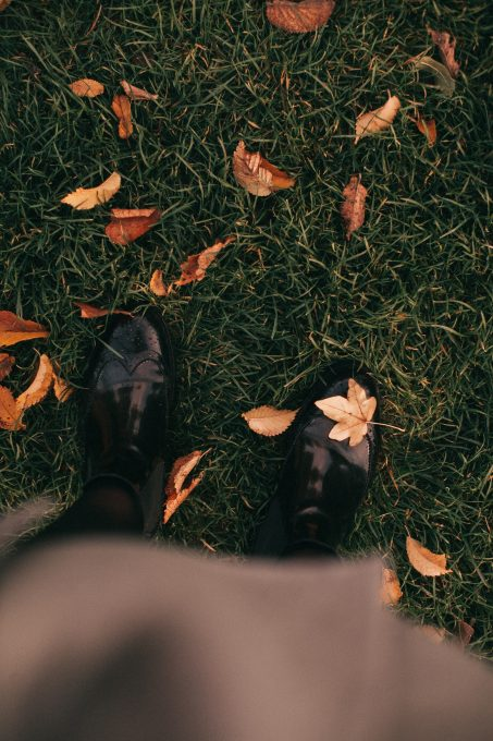 A person wearing black shoes standing on grass