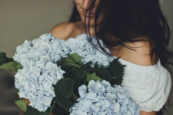 A woman holding blue flowers