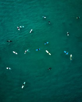 Aerial view of people using surfboards waiting for sea waves