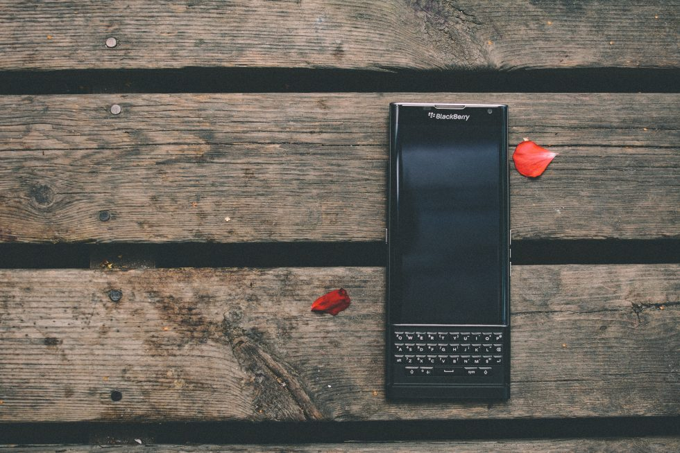 Black Blackberry qwerty phone lying on a wooden table