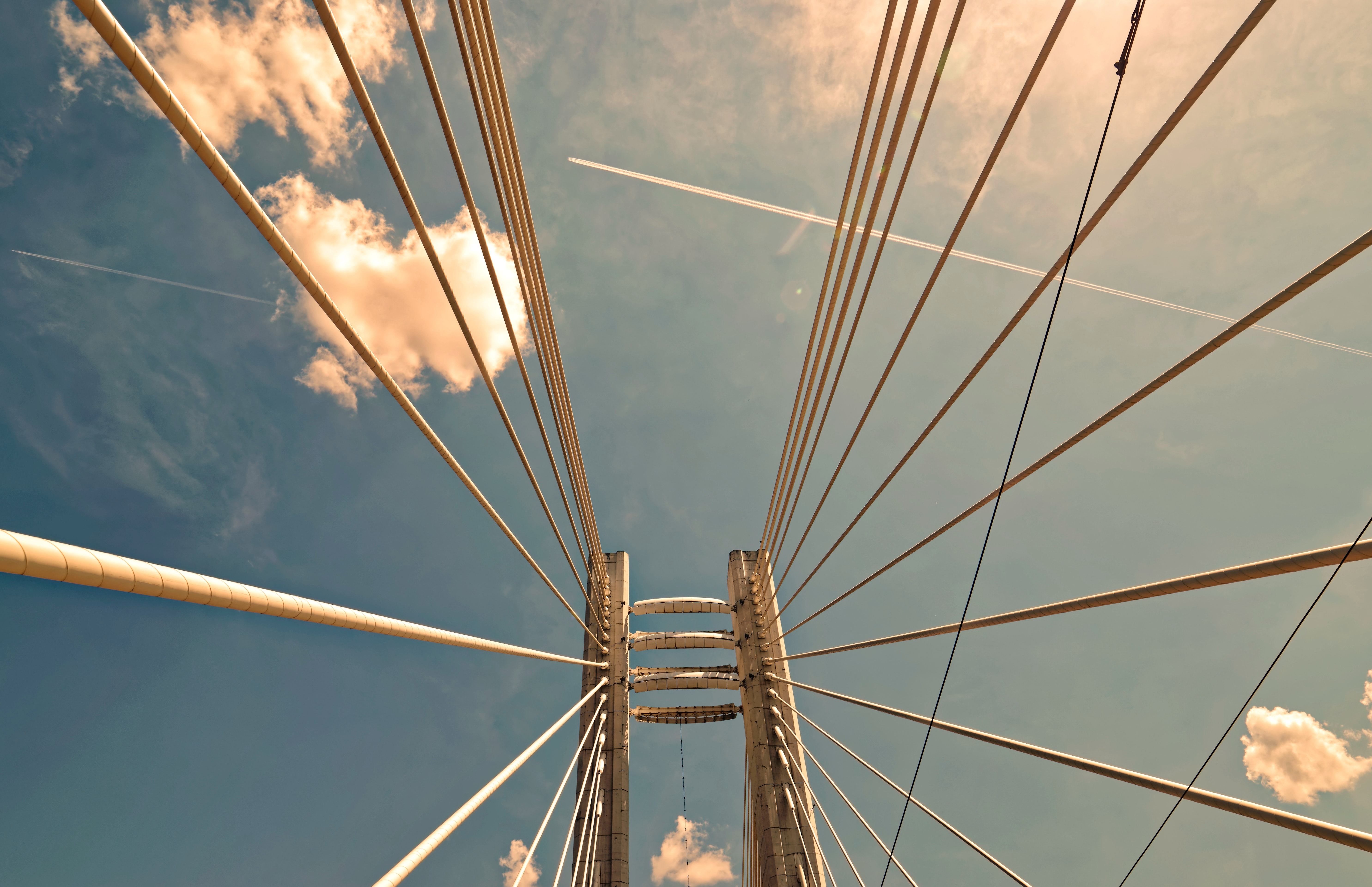 Low angle photo of a bridge under a blue sky and white clouds
