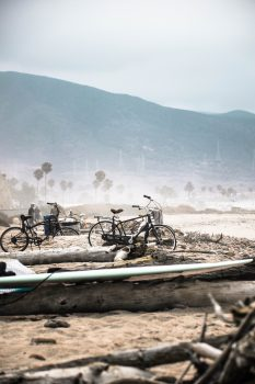 Two bicycles parked beside a log near shore