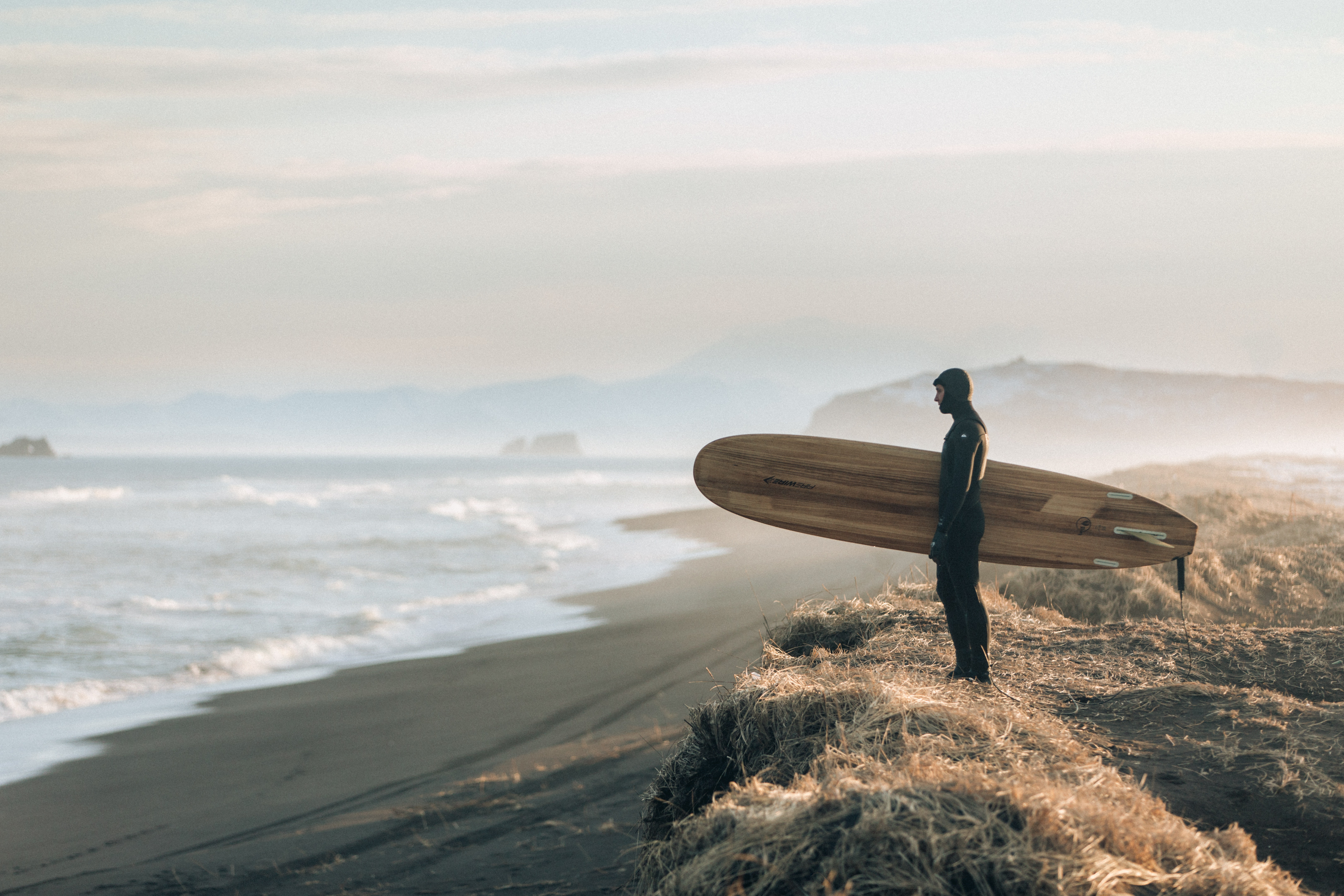 A man holding a surfboard and looking at the sea