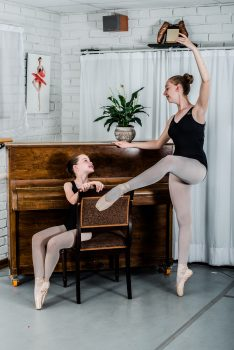 Two ballerinas near a piano