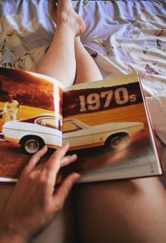 A person holding a car book on his lap