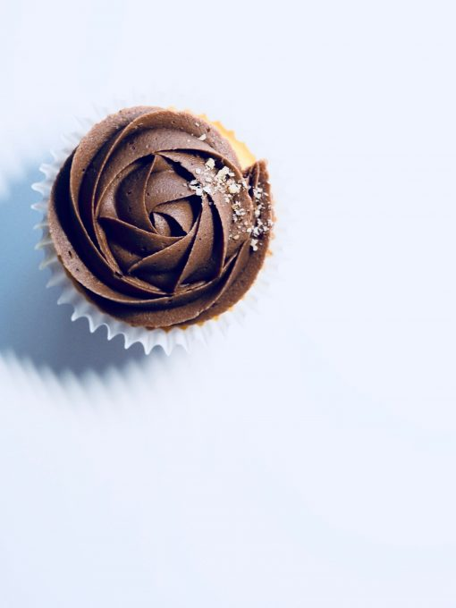 Flat view of a chocolate cupcake on a white surface