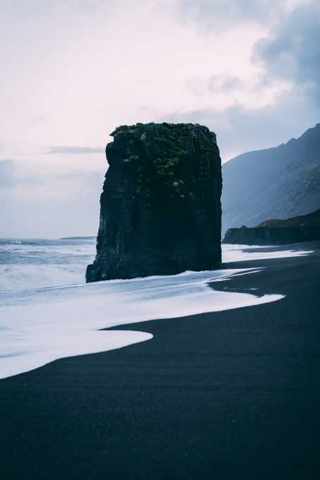 A black rock formation near the sea