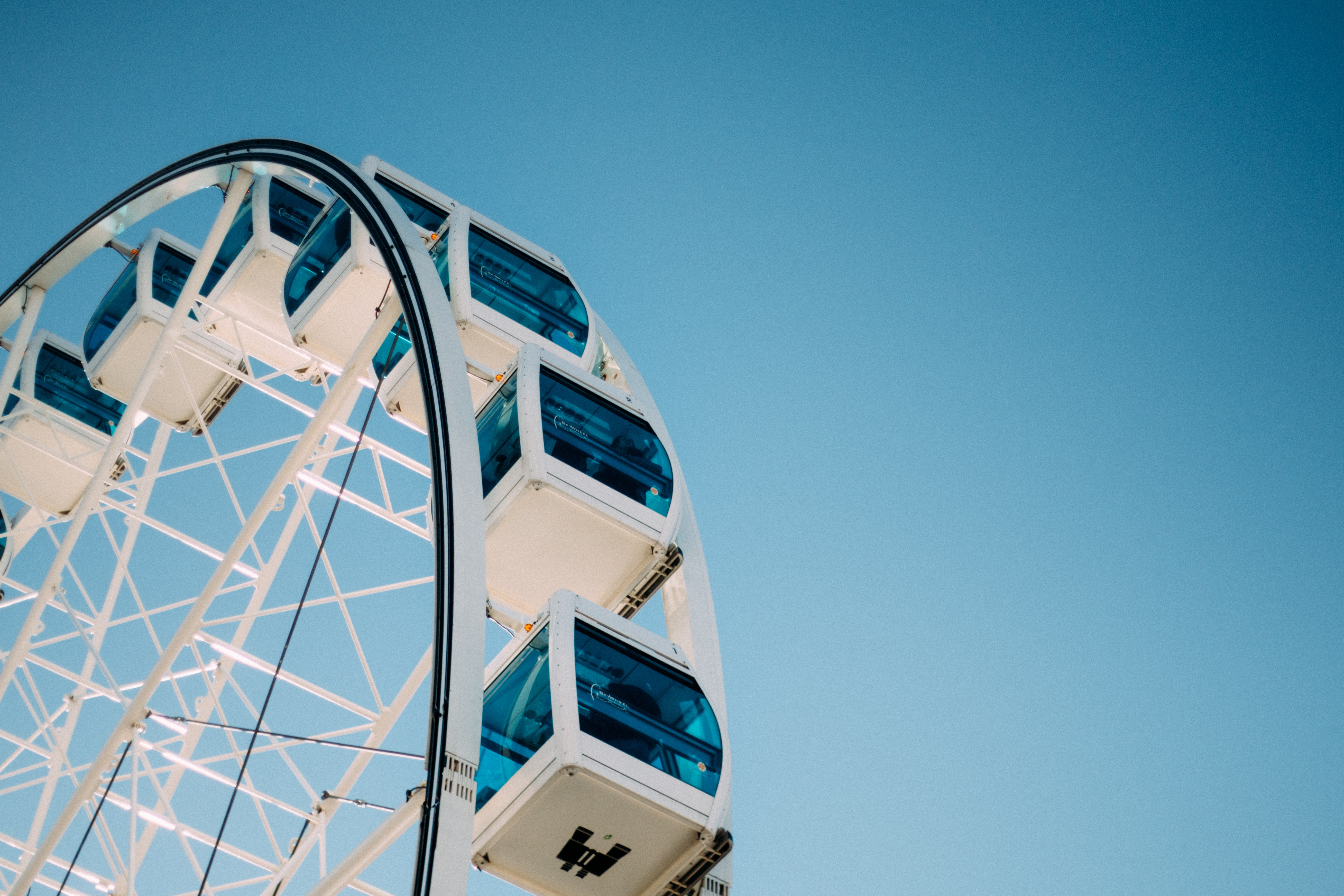 A blue and white Ferris wheel under a blue sky