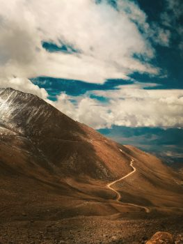 A brown mountain under white clouds