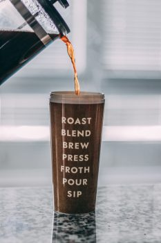 A brown tumbler filled with coffee