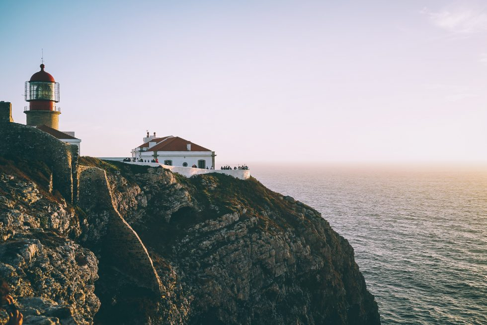 A lighthouse on a cliff beside the body of water