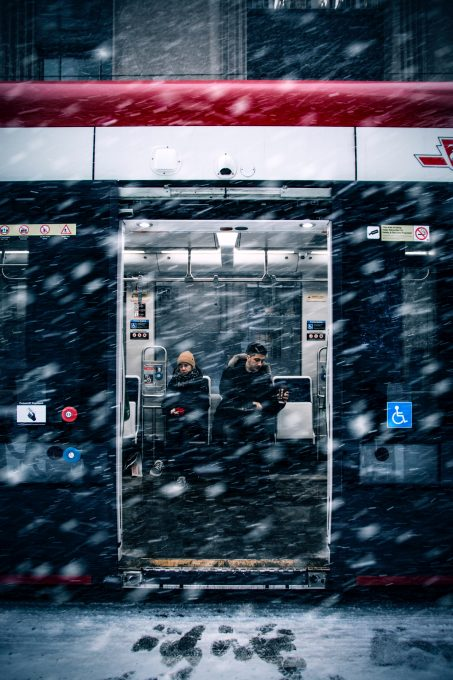 A man beside a woman in a train during snowfall