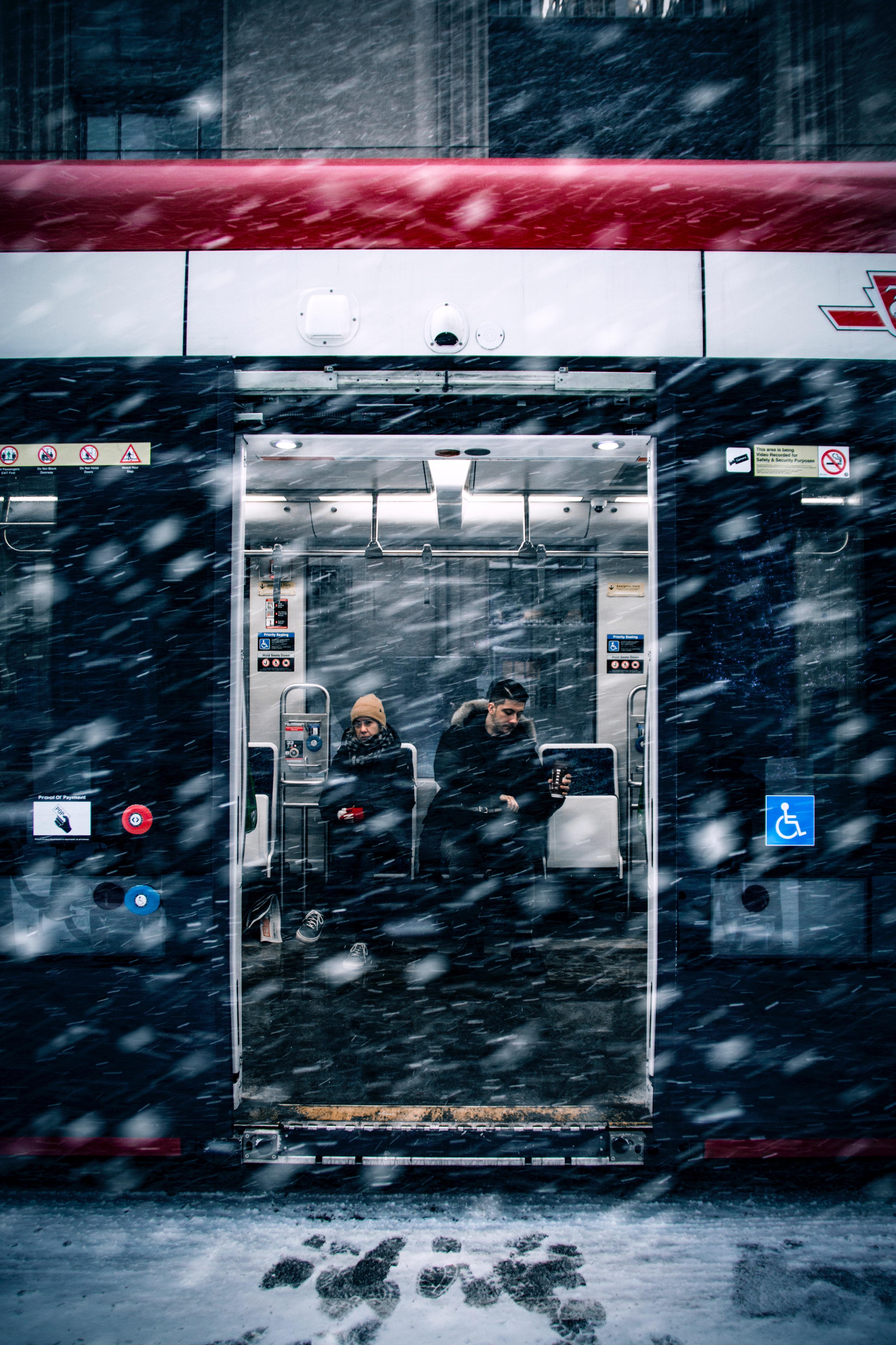 A man beside a woman in a train during snowfall