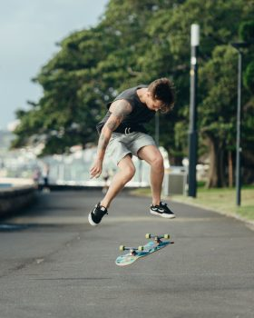 A man in a black tank top on a road doing skateboard tricks