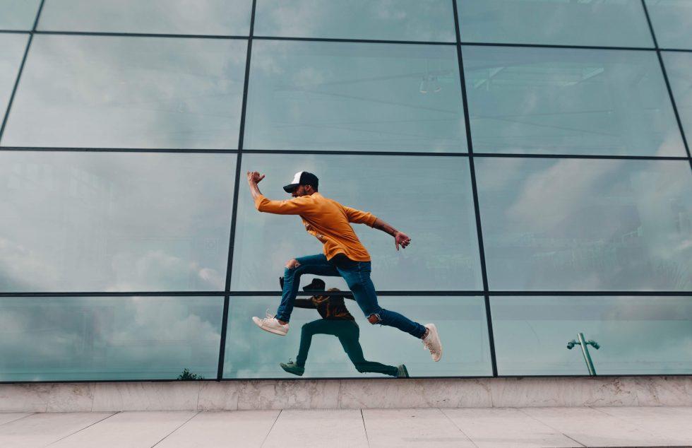 A man running beside a mirror wall
