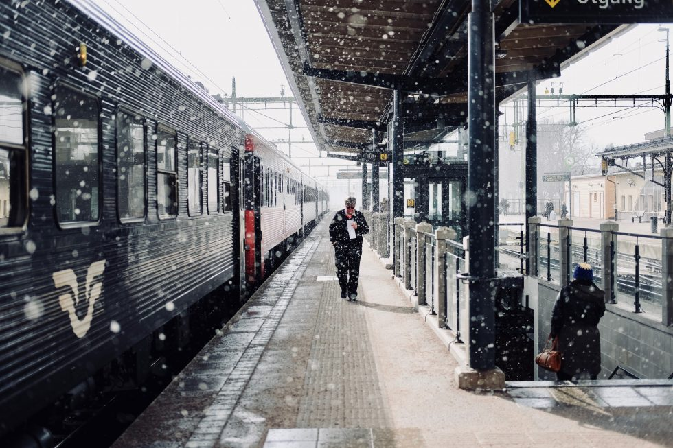 A man walking beside a train during snowfall