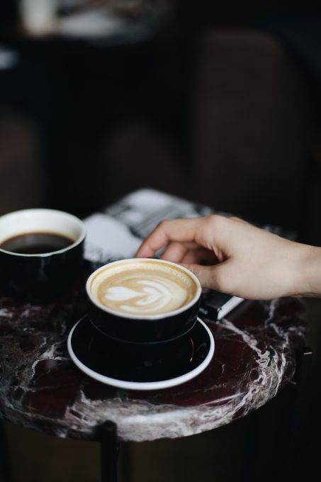 A person holding a cup of cappuccino