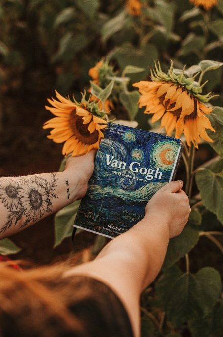 A person holding a Van Gogh book beside sunflowers