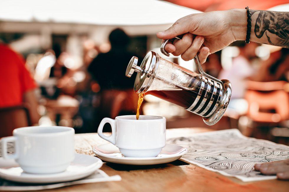 A person pouring tea into a white ceramic cup