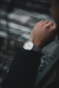 A person wearing a round analog watch