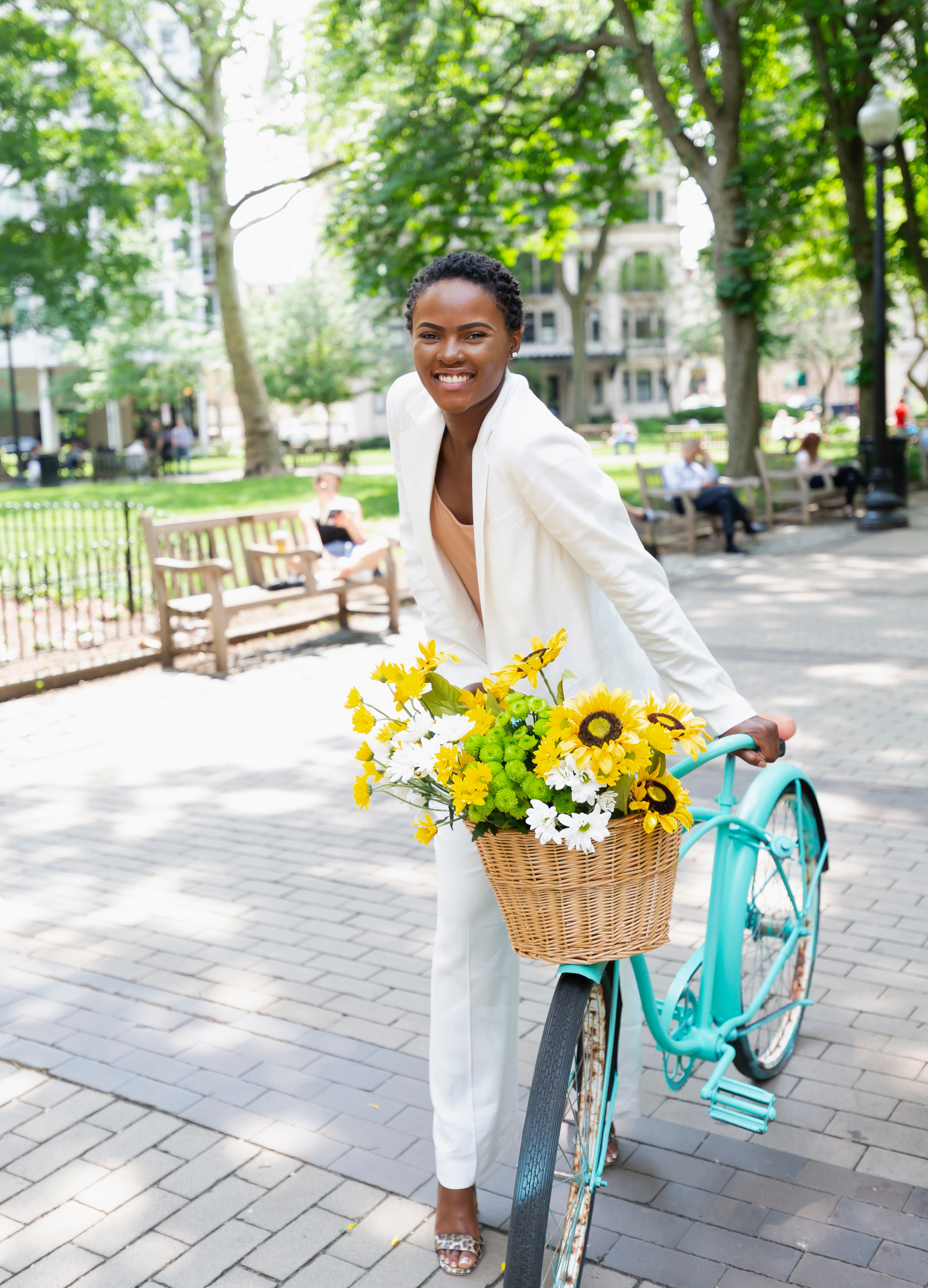 A smiling woman holding a blue cruiser bike with a basket of flowers
