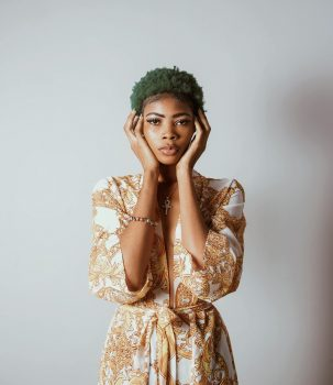 A standing woman with green hair holding both hands on her face