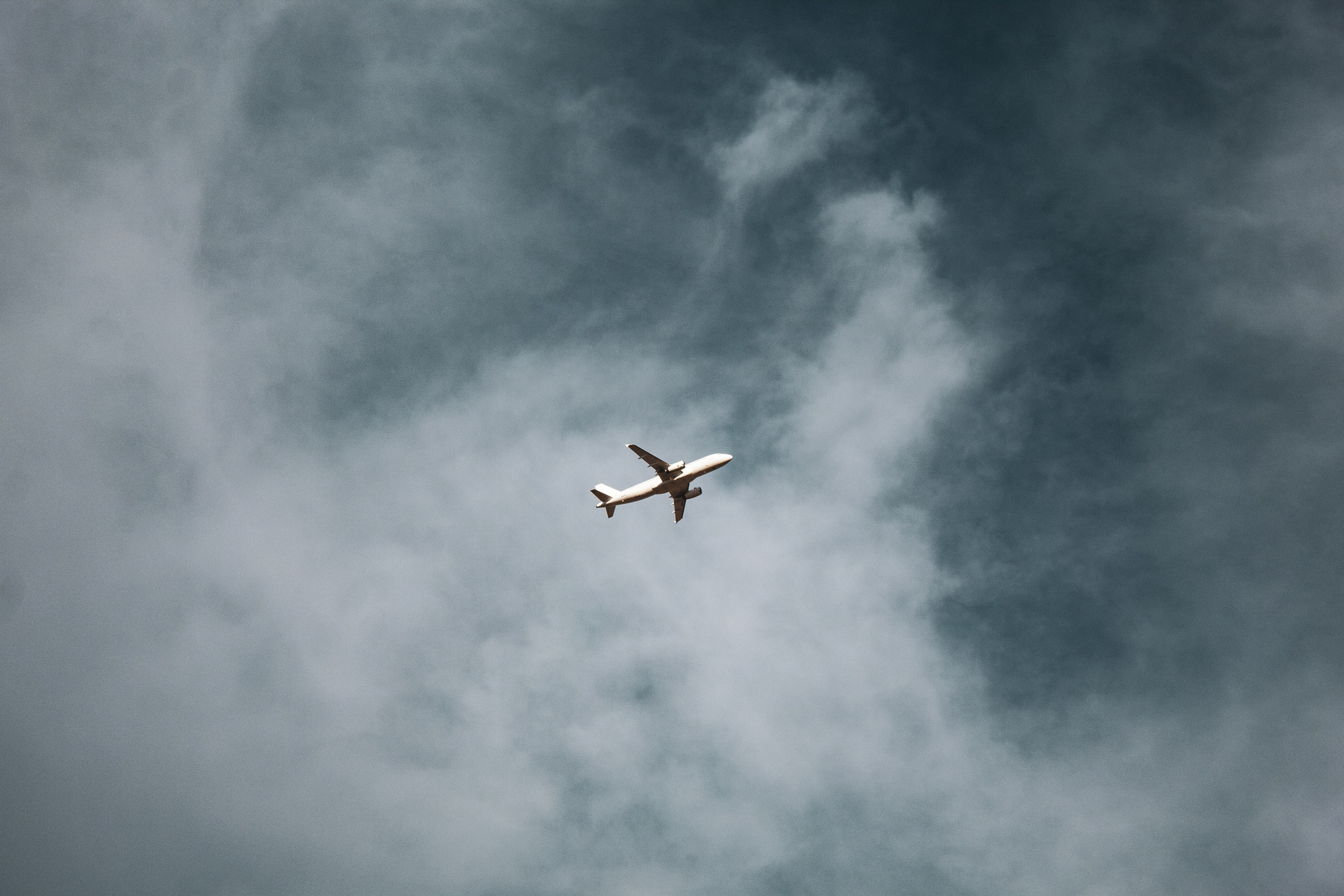 A white plane on air under a cloudy sky