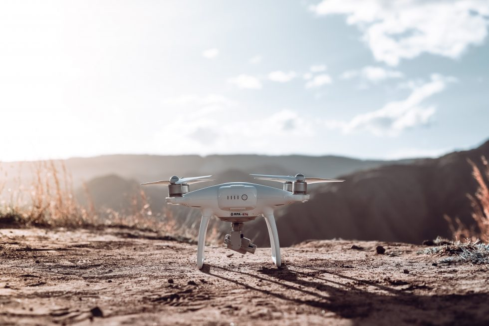 A white quadcopter drone on top of brown soil