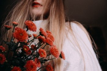 A woman holding red flowers