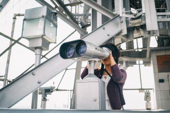 A woman in a purple cardigan using binoculars