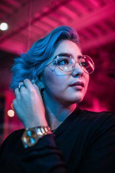 A woman in eyeglasses wearing a black top