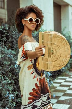 A woman in sunglasses wearing a white and brown floral dress