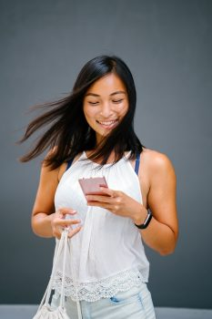 A woman using a phone while carrying a bag