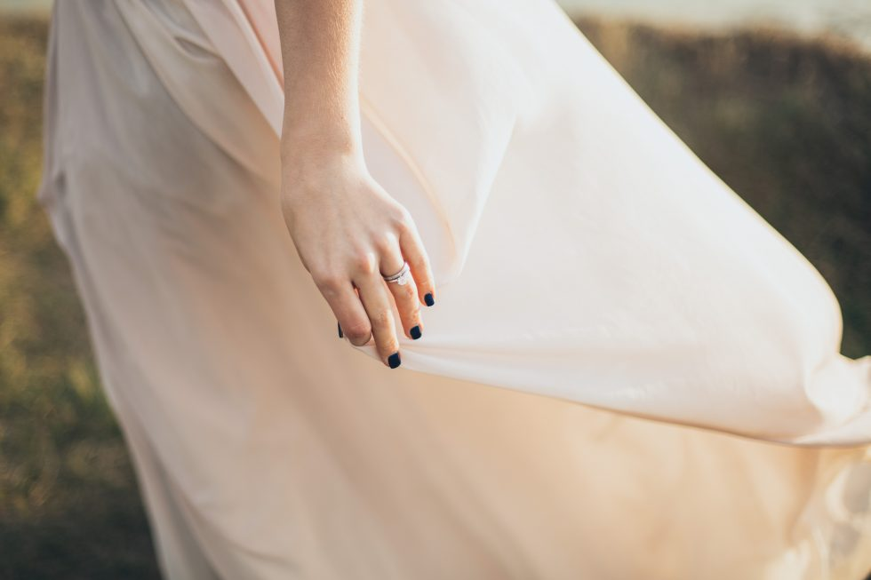 A woman wearing a white dress with black manicure