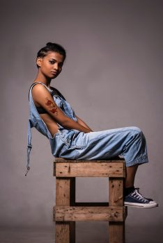 A woman wearing dungarees posing on a wooden stool