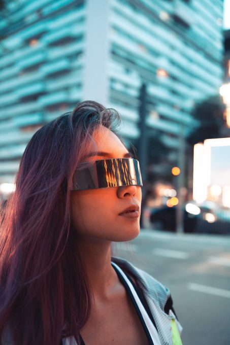 A woman wearing futuristic sunglasses near high-rise buildings