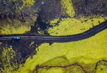 Aerial view of a car crossing over an Icelandic black lava field