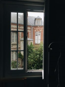 An open window overlooking a red building