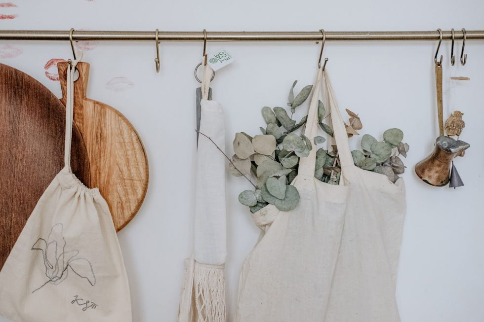 Aprons, a chopping board, and bag hanging on a white painted wall