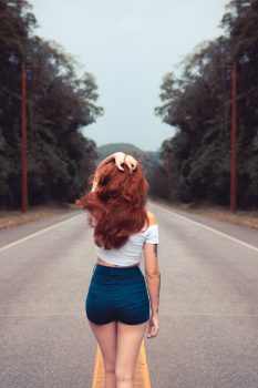 Back view of a woman standing on a road