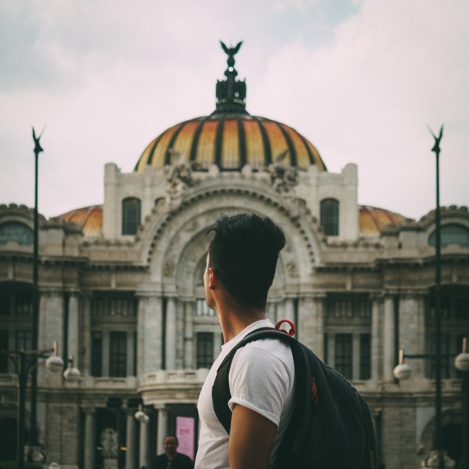 Back view of a young man standing near a building