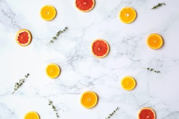 Flat lay photography of sliced citrus fruits on a marble surface