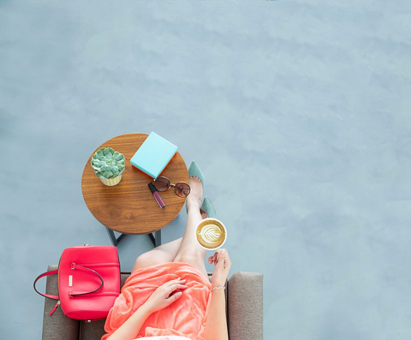 Flatlay photo of a woman sitting on a sofa chair holding a cup of coffee