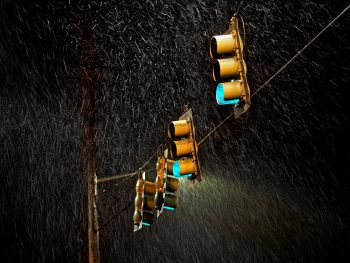 Four traffic lights under the rain during night time